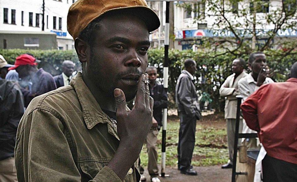 """Michael Kakungi er 33 år og har røget, siden han var 19 år. Han er overbevist om, at rygeloven ikke vil få folk til at stoppe, kun til at ændre rygevaner, og så vil loven have en positiv inflydelse på politibetjentes privat-økonomi. Skiltet med teksten """"smoking zone"""" ses i baggrunden,–"""