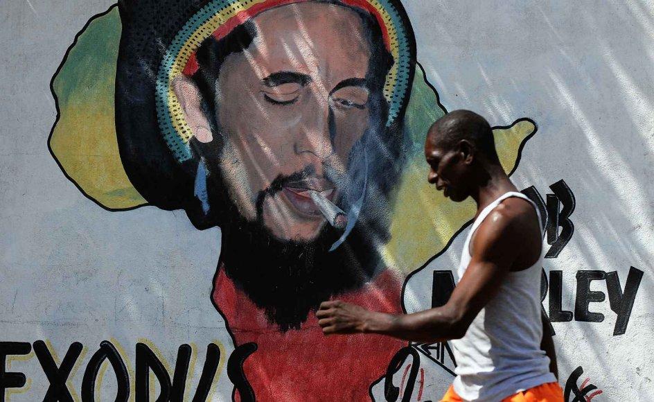 Billede fra Jamaicas hovedstad Kingston. Bob Marley, der er portrætteret på muren, er den mest berømte rastafari. Tilhængere af bevægelsen har ofte lange dreadlocks og bærer de etiopiske farver rød, gul og grøn.