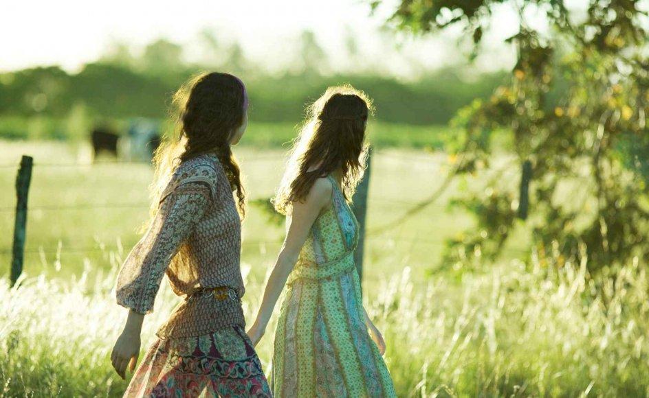 Young hippie women walking through field