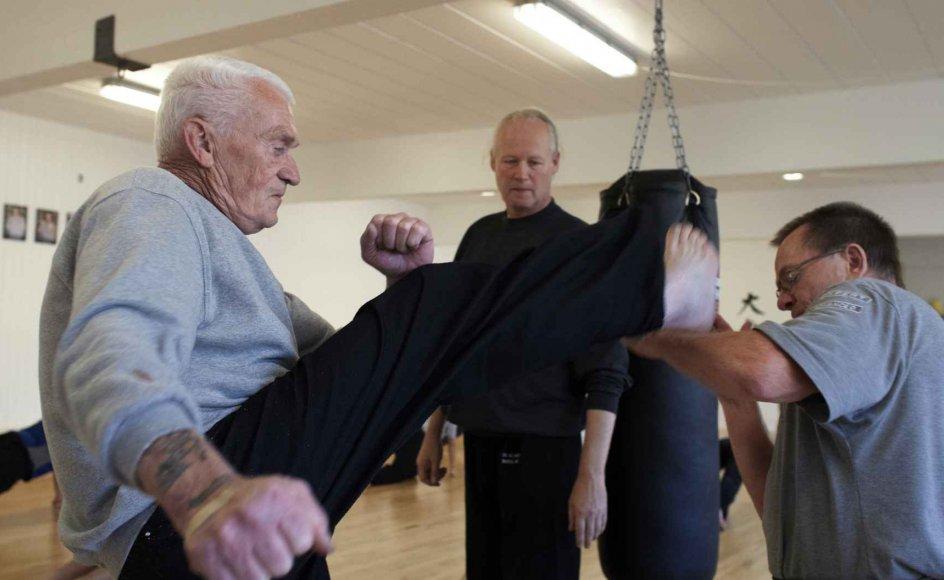 """Den 70-årige Ole Peter Bangsgaard, eller """"Bangs"""" som han bliver kaldt i selvforsvarsklubben, har ingen problemer med stive led eller forpustethed. Her må klubkammeraten, den 57-årige Hans-Jørn Bertelsen (th.) parere et målrettet spark, mens træner Kurt Ørum ser på.–"""