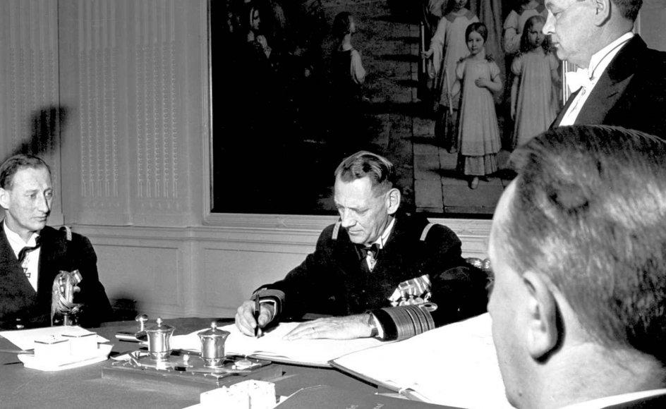 Kong Frederik IX (1899-1972) underskriver Grundloven af 1953, som betyder, at kongens ældste datter bliver dronning, når han dør. Til venstre sidder arveprins Knud (1900-1976), som indtil Grundlovens indførelse var tronarving, da kvindelig arvefølge ikke var mulig før 1953. –