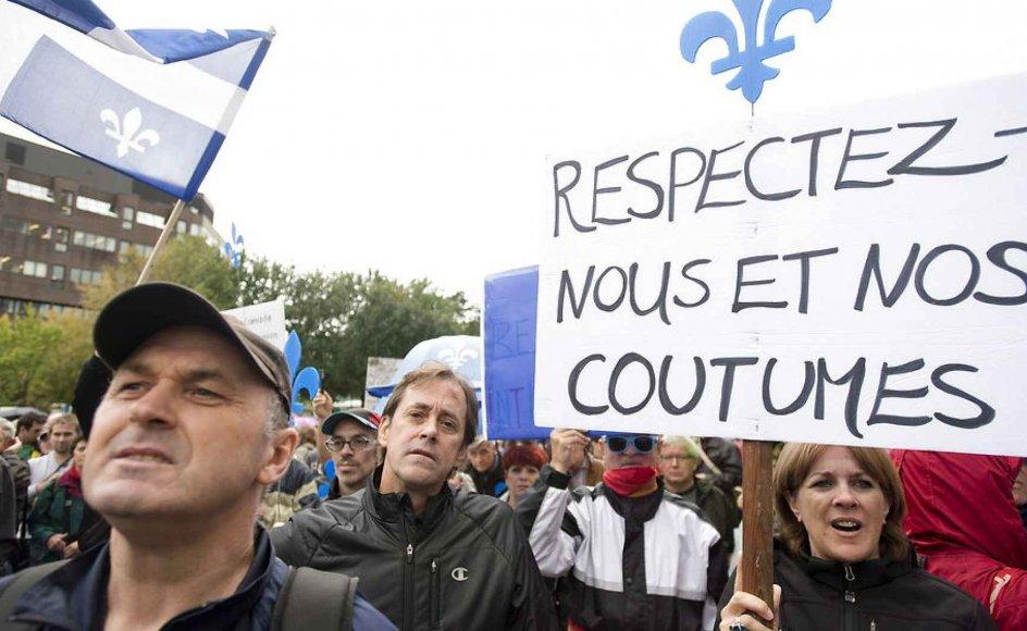 'Respektér os og vores skikke,' står der på skiltet, som fulgte en pro-demonstration for tilhængere af det kontroversielle forslag om en begrænsning af retten til at bære religiøse symboler i Québec. Forslaget, som kommer fra provinsens mindretalsregering, har delt vandene i den overvejende fransktalende del af Canada. Billedet er fra en demonstration den 22. september 2013.