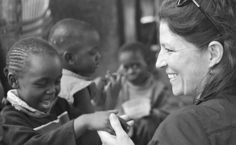 """Swaziland i Afrika er det land i verden, som er hårdest ramt af aids. Bibelselskabernes program for at hjælpe de børn, som har mistet deres forældre og måske selv har fået aids, har fået navnet """"Den barmhjertige samaritaner"""". På billedet er det Synne Garff sammen med udsatte børn i byen Manzini. –"""