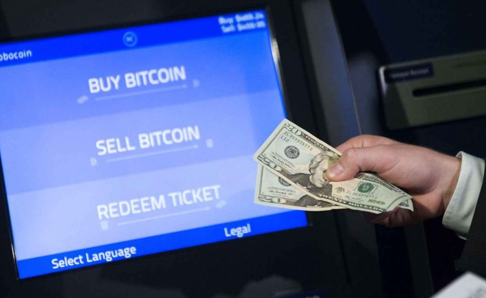 Robocoin CEO Jordan Kelley demonstrates how to buy and sell bitcoins during a demonstration of a Robocoin kiosk on Capitol Hill in Washington, DC, April 8, 2014. Robocoin is the world's first bitcoin kiosk for buying and selling the digital currency. AFP PHOTO / Saul LOEB