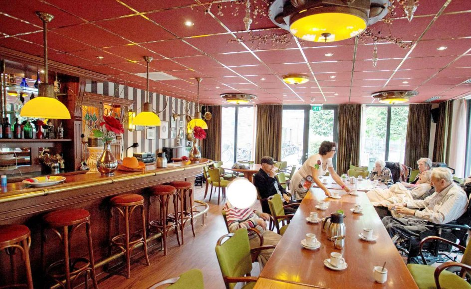 Hollandsk populær musik af ældre dato strømmer ud fra baren på De Hogeweyk, hvor en gruppe beboere er samlet denne formiddag. Plejehjemmet har en ambition om at aktivere og inddrage beboerne. Kvinden i midten af billedet er anonymiseret efter ønske fra de pårørende. Alle fotos: Maartje Geels.