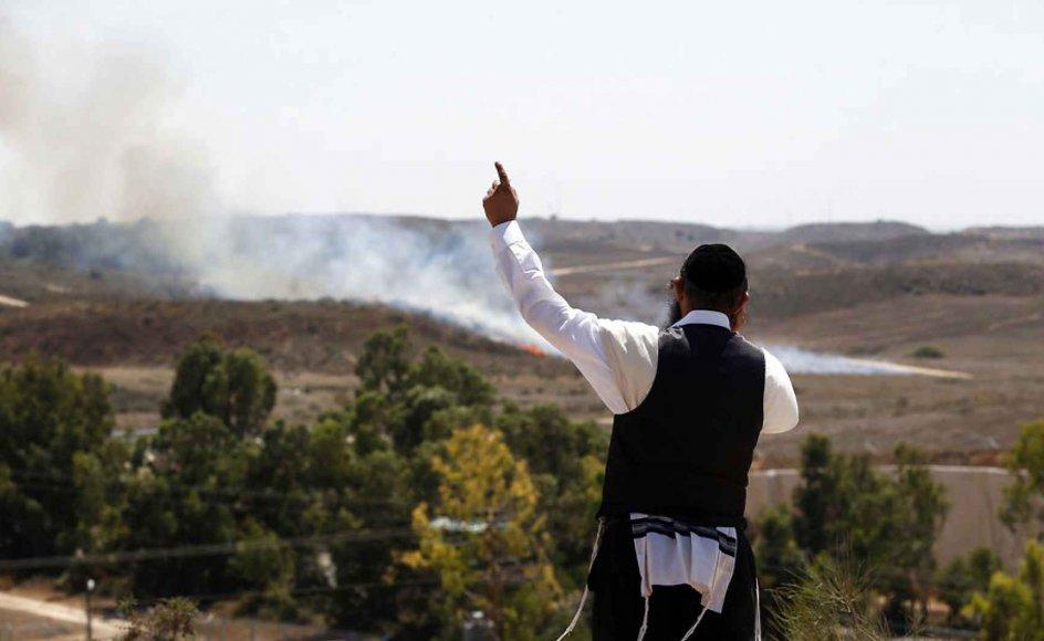 """""""Vi er her for at se Israel smadre Hamas,"""" siger Eli Chone, en 22-årig amerikaner, der bor i Israel. På billedet ser en ortodoks jøde til, mens en bombe affyret fra Gaza lander tæt på den israelske by Sderot. Gazas affyringer af bomber mod Israel har de seneste dage ført til voldsomme israelske luftangreb på det Hamas-kontrollerede område."""