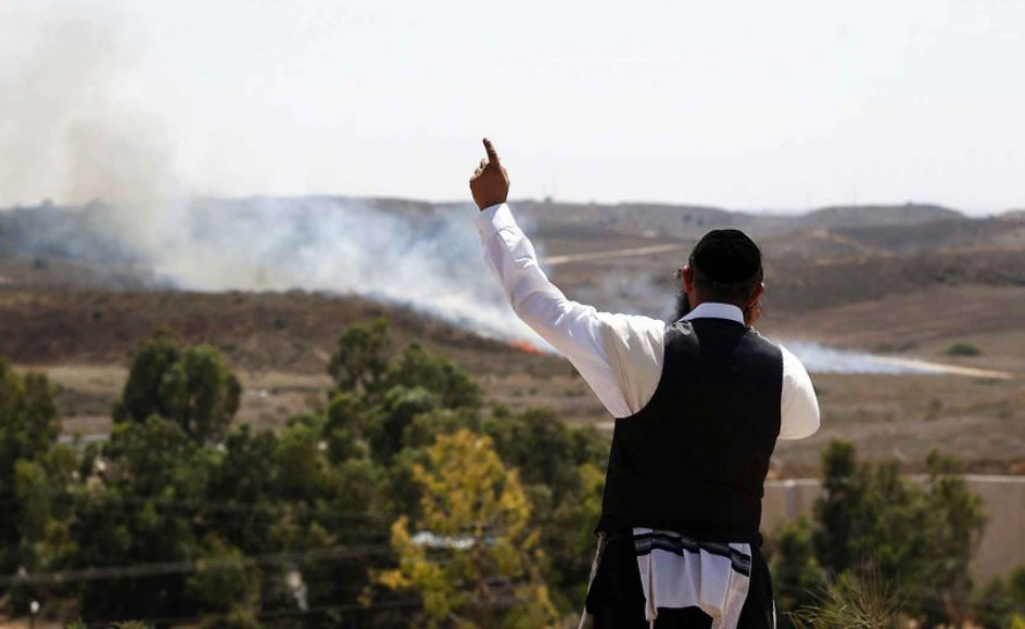 """""""We are here to see Israel destroy Hamas,"""" says Eli Chone, a 22-year-old American living in Israel. The picture shows an orthodox jew gesturing as a bomb fired from Gaza lands near the Israeli town of Sderot. Gaza's firings of bombs against Israel has in recent days led to massive Israeli air strikes on the Hamas-controlled territory."""