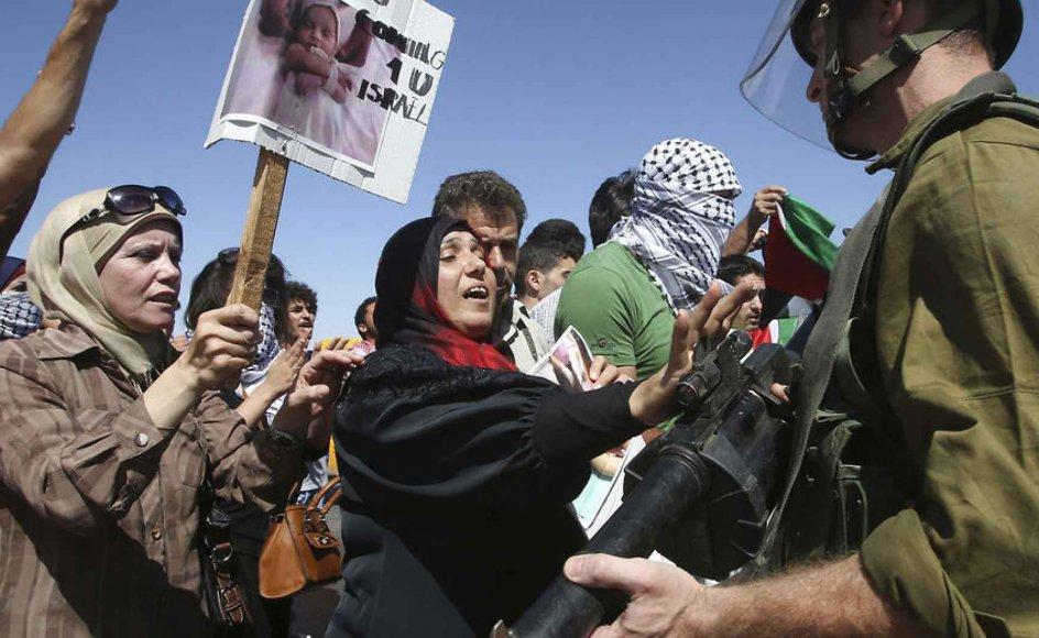 Palæstinensiske demonstranter på Vestbredden nær byen Nablus toppes med israelske soldater under en protest  mod israelske luftangreb på Gaza, der foreløbig har kostet omkring 180 palæstinensere livet.