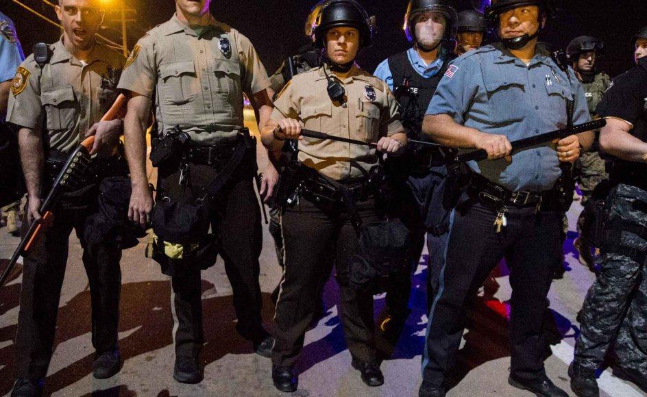 Lokalt politi i forskellige kampuniformer står klar under et af de seneste ugers natlige sammenstød i kølvandet på konflikten, der blev udløst af nedskydningen af den sorte unge mand Michael Brown i Ferguson. I byen var der i 1990 30 procent sorte og 70 procent hvide. I dag er det lige omvendt. De rige hvide er flyttet fra byen, men det er ifølge Jacob Holdt de samme betjente, som har været der hele tiden, siden byen var overvejende hvid, og som ikke er flyttet væk. -