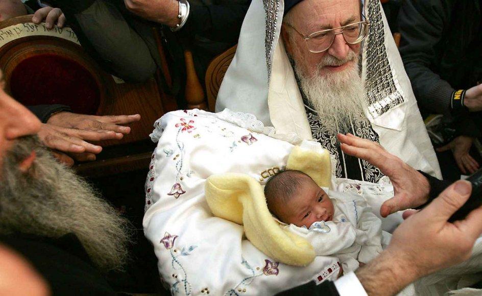 Israels Rabbi Mordechai Eliyahu bærer et otte dage gammelt spædbarn under en omskærelses-ceremoni foran det israelske parlament Knesset. En tradition, som nu bliver udfordret. Israels Højesteret besluttede i begyndelsen af sommeren, at en mor ikke behøvede at omskære sit barn.