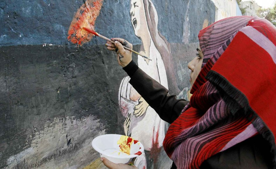 En palæstinensisk pige i færd med at male en vægmaleri i Gaza med en grædende kvinde - en reference til den israelske offensiv mod området i juli og august. I søndags sluttede en donorkonference med tilsagn om 5,4 milliarder dollars (knap 32 milliarder kroner) til genopbygningsarbejdet i Gaza -