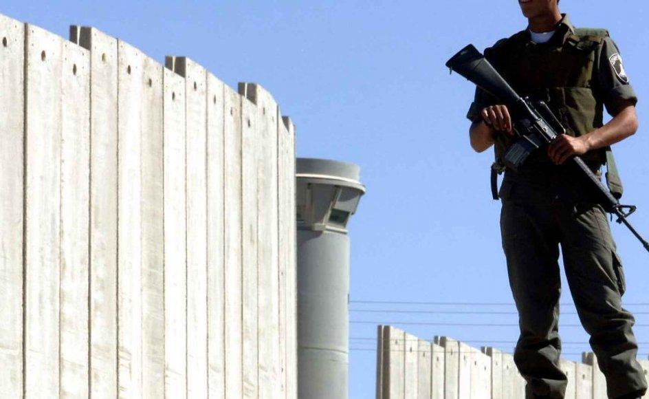 En israelsk grænsevagt står ved muren, der deler Israel og Vestbredden, tæt ved indgangen til Jesu fødeby Betlehem.