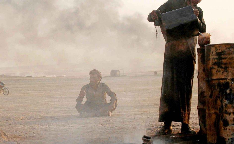 Islamisk Stat kontrollerer mange olieraffinaderier - her et primitivt et af slagsen nær bevægelsens syriske hovedby, Raqqa - men olien er blot en af mange indtægts-kilder for terrorbevægelsen. -