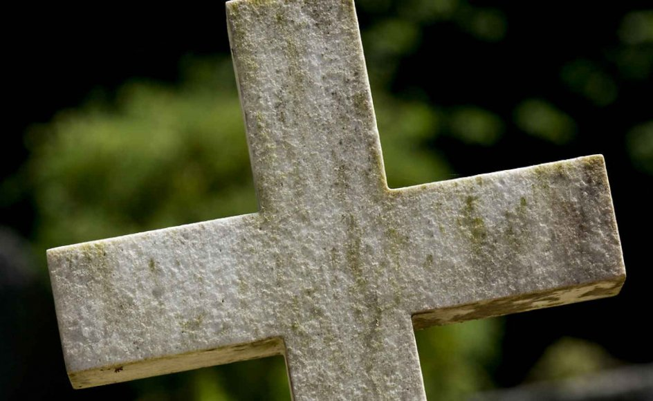 Kors som gravsten på gravsted på kirkegården. Ormslev Kirke ved Aarhus i solskin.