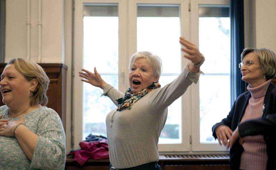 I midten ses 70-årige Elinor Haller, en tidligere kræftpatient på Røde Kors-sygehuset i Berlin, der føler sig overbevist om sangens helende kraft. -