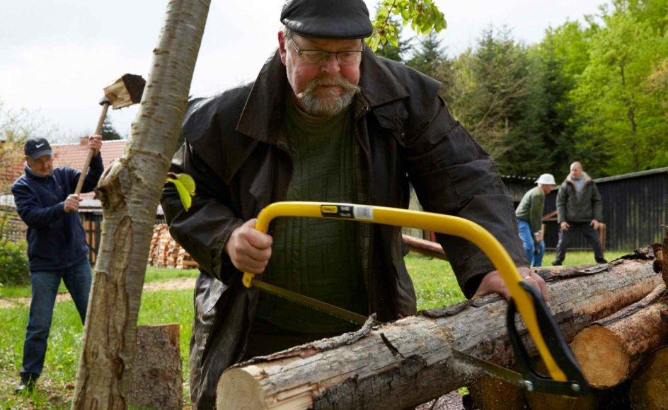 Hver mandag og onsdag tilbringer gruppen af kræftramte mænd formiddagen sammen her i skoven. De koger kaffe over åben ild, de laver udendørs fitness med øksesvingning og mavebøjninger på brændestabel, og de hjælper til med at rydde uønskede småtræer væk i skoven ned mod en nærliggende sø.