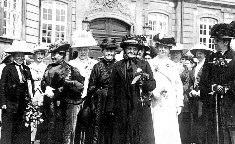 Den 5. juni 1915 samledes over 12.000 kvinder på Amalienborg Slotsplads for at fejre, at de gennem en grundlovsændring endelig kunne stemme ved folketingsvalg. Kvinden med blomsterbuket er kvindesagsforkæmper Jutta Kunigunde. Klik på pilene i billedet for at se omslaget til bogen.