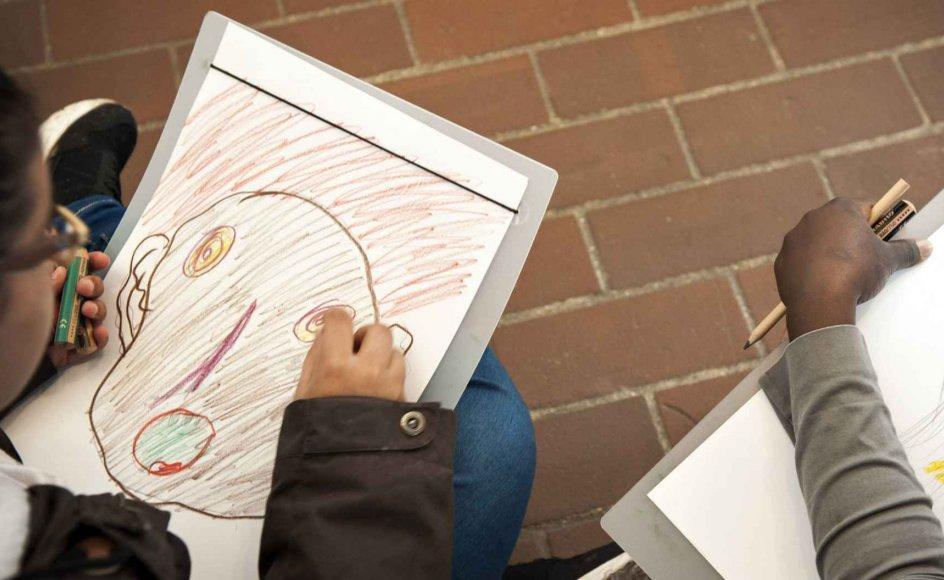 """En gruppe børn og unge fra Skolen på Bakken i Nordsjælland i færd med at tegne efter inspiration fra Asger Jorns billede """"Dobbelt-ansigt"""". Undervisningen på kunstmuseet er et afbræk fra den ofte hårde hverdag i asylcenteret. Klik på pilene i siden af billedet for at se et billedet mere."""