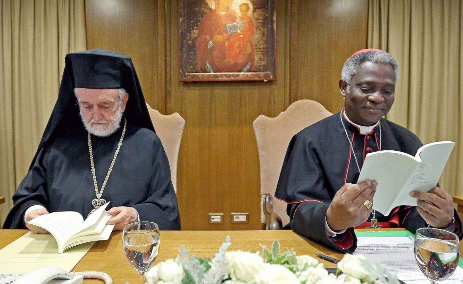 Den græsk-ortodokse metropolit af Pergamon, Joannis Zizioulas (til venstre), og den ghanesiske katolske kardinal Peter Kodwo Appiah Turkson læser i pavens rundskrivelse under præsentationsmødet i går i Vatikanet.