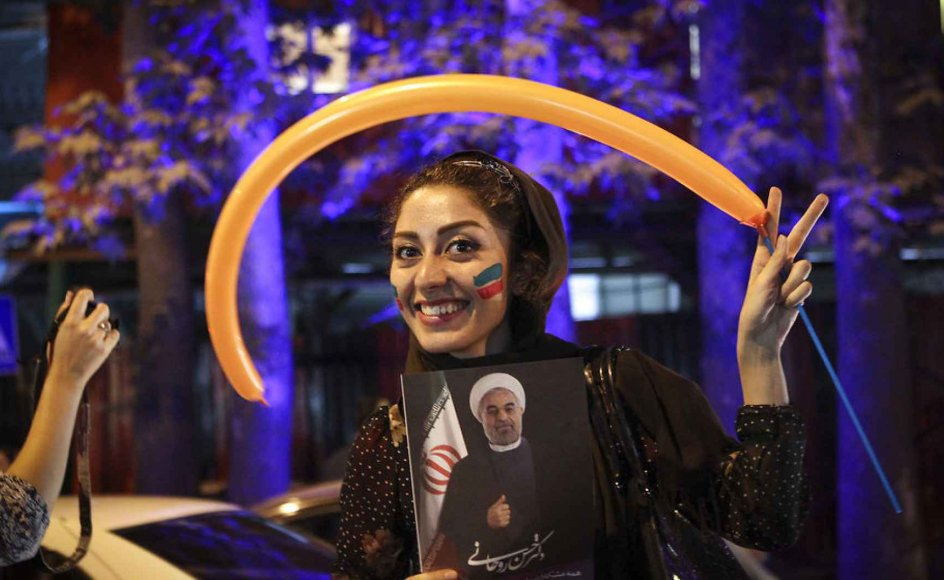 En iransk kvinde fejrer atomaftalen i Teheran med balloner og ansigtsmaling. Iran har været ude i kulden siden den islamiske revolution i 1979, og landet er hårdt medtaget af internationale sanktioner. En atomaftale vil få USA og Vesten til at lempe mange af de økonomiske sanktioner.