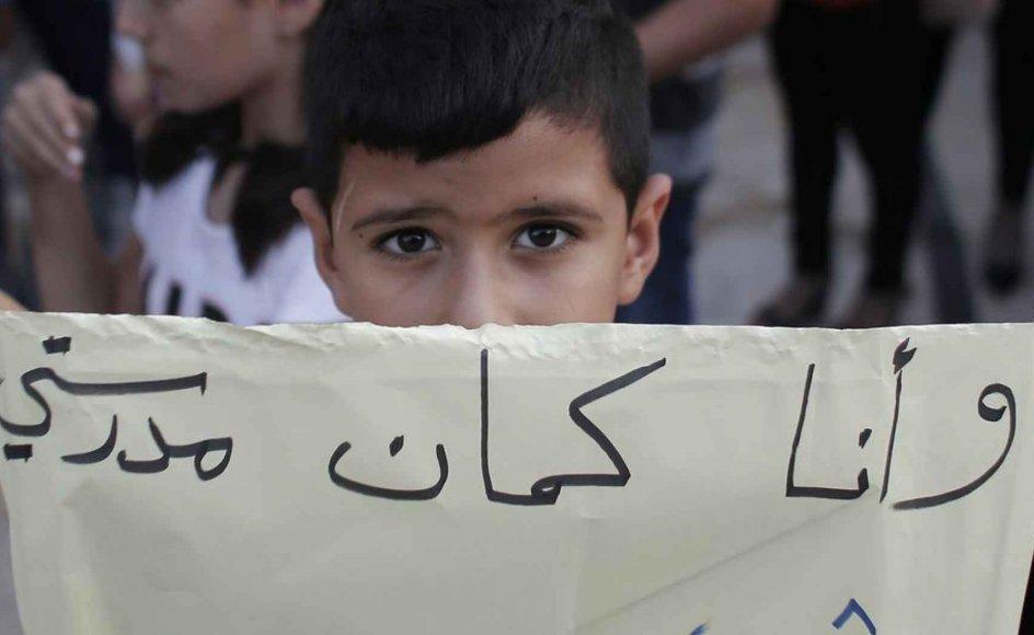 """En ung dreng demonstrerer under skolestrejken med et banner med arabisk påskrift, som oversat betyder """"Også mig... Min skole er ikke til salg"""""""