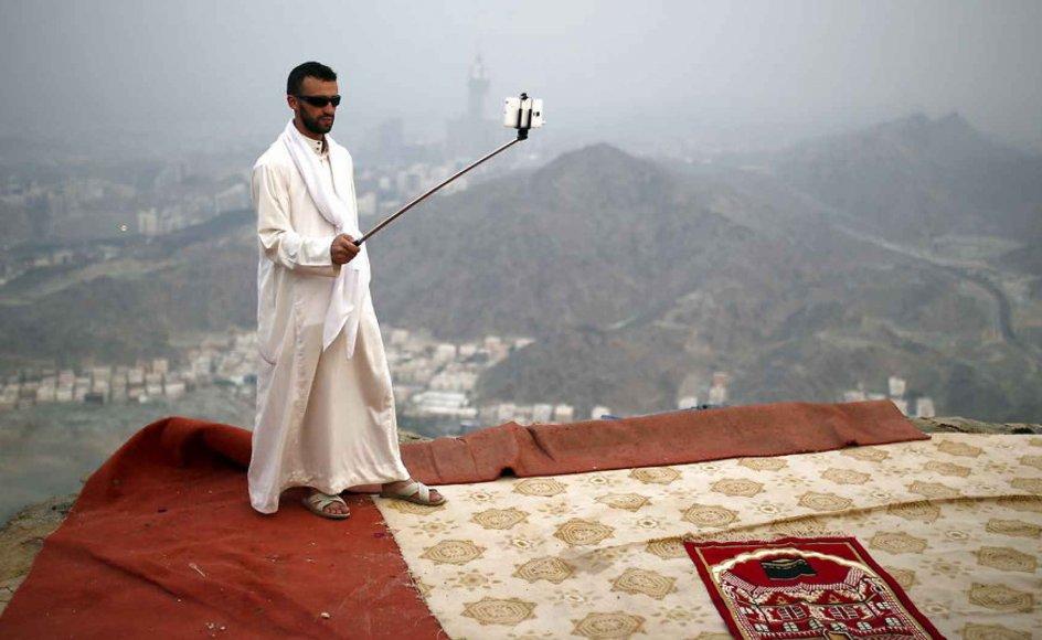 En muslimsk pilgrim tager en selfie med en såkaldt selfie-stang på toppen af et bjerg ved den hellige by Mekka i Saudi-Arabien. Et par skridt bagud, og han ville formentlig styrte i døden. Det er desværre sket for en del mennesker. -