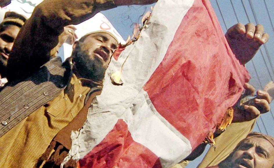 12 karikaturtegninger af muslimernes profet Muhammed blev offentliggjort i Jyllands-Posten den 30. september 2005. Fem måneder senere, i februar 2006, var der voldsomme protester i Mellemøsten og Asien. Her holder aktivister fra den pakistanske bevægelse Jamaat Ulema-e-Islam et brændende flag under en demonstration i Lahore, Pakistan den 3. februar 2006. -