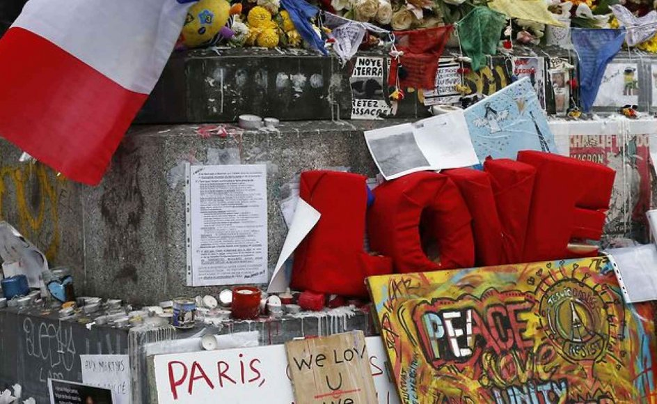 """A picture taken on November 27, 2015, shows French national flags, candles and flowers at a makeshift memorial in Place de la Republique square in Paris, for the National Tribute to the 130 people killed in the November 13 Paris attacks. Families of those killed in France's worst-ever terror attack, claimed by the Islamic State (IS) group, will join some of the wounded at ceremonies at the Invalides, the gilded 17th-century complex in central Paris that houses a military hospital and museum and Napoleon's tomb. The tribute will be """"National and Republican, """" an official at the Elysee presidential palace said, referring to the French republic's creed of liberty, equality and fraternity. AFP PHOTO / THOMAS SAMSON"""