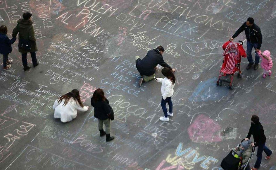 Borgere i Bruxelles skriver beskeder med ønsker om fred og tanker til de efterladte på asfalten ved Place de la Bourse efter terrorangrebet i byen.