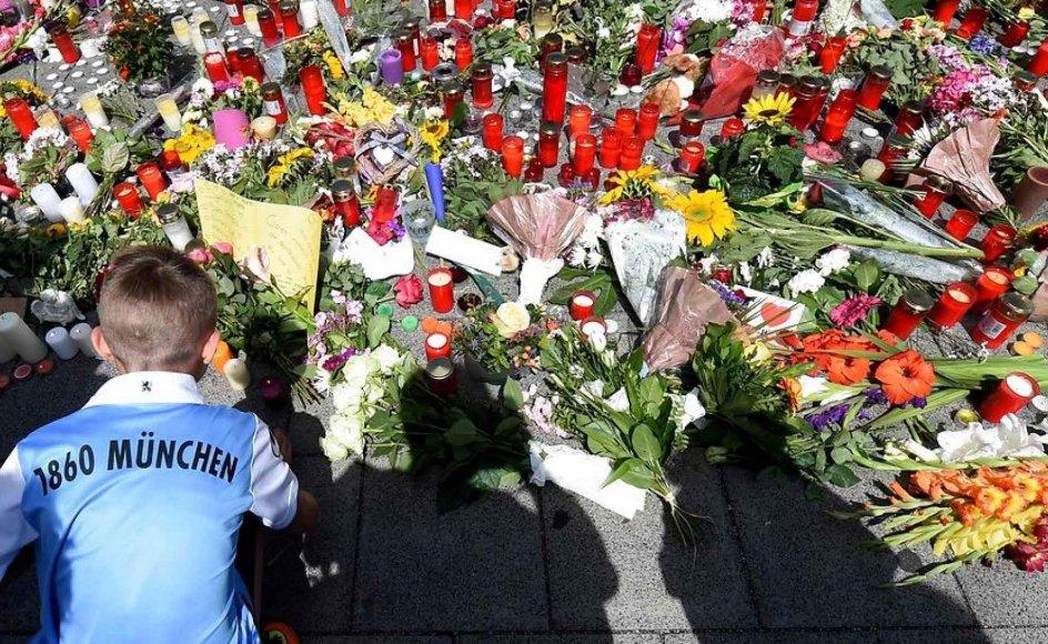 En dreng knæler foran det blomsterhav, der er blevet lagt foran det indkøbscenter, hvor 18-årige David Ali Sonboly sidste fredag dræbte ni mennesker.
