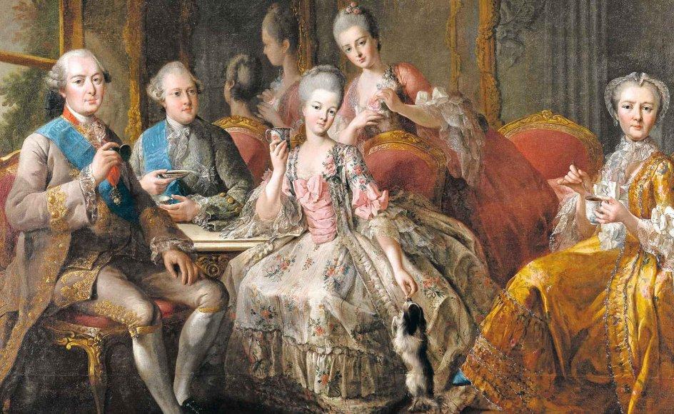 Jødiske handelsmænd bragte chokoladen til fine folk i 1700-tallet. Her ses et fransk selskab drikke datidens modedrik, der blev fremstillet ved at koge hårdt- presset kakaomasse sammen med vand. Bemærk, hvordan det på den tid var acceptabelt (for mænd) at drikke af underkop, mens damerne drikker chokolade af særlige høje chokolade- kopper. – Maleri: Jean-Baptiste Charpentier 1768/ Musée de Versailles.