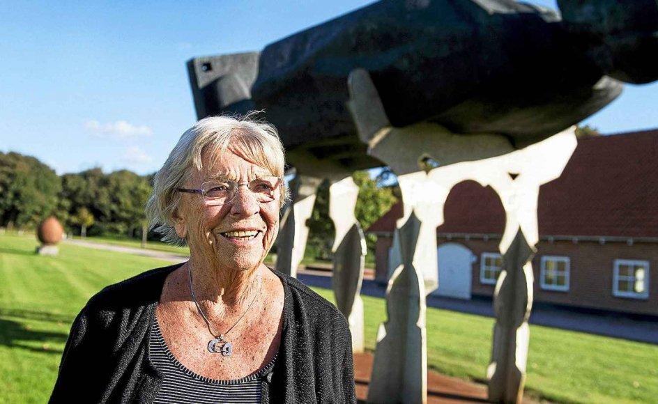 Bitten Damgaard er som 89-årig stadig meget aktiv inden for både kunst, kultur og kirke. Her er hun fotograferet foran hendes hjem, den nedlagte præstegård i Gjellerup, med en Lenin-statue lagt på lit de parade i baggrunden. Den blev hentet hjem på initiativ af hendes afdøde mand, da Sovjet-styret kollapsede i Letland. –