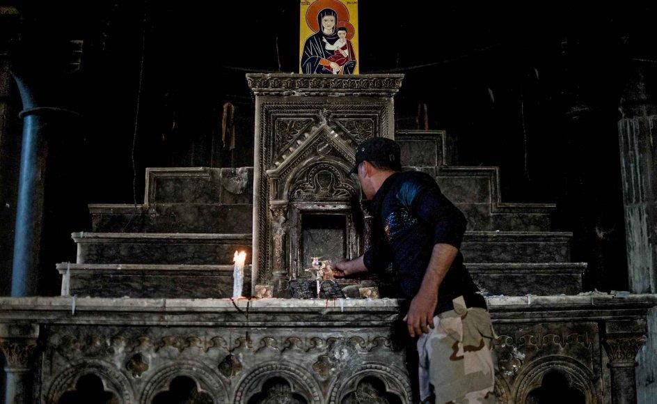 En kristen, irakisk soldat tænder et lys i en udbrændt kirke i den nordirakiske by Qaraqosh. Byen blev befriet fra IS tidligere på efteråret. Alligevel tvivler mange af byens kristne på, om de igen tør flytte tilbage. –