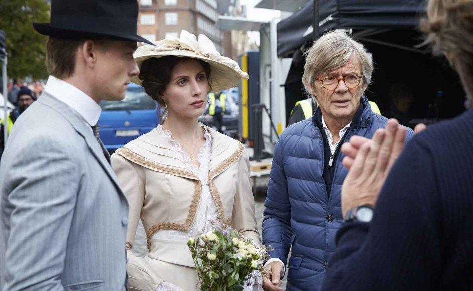 """Optagelser til filmen """"Lykke-Per"""", der instrueres af Bille August. Skuespiller Katrine Greis-Rosentahl, som spiller Jacobe ses i lys kjole, og Esben Smed ses iført jakkesæt og hat. Filmen får ros af de fleste anmeldere."""