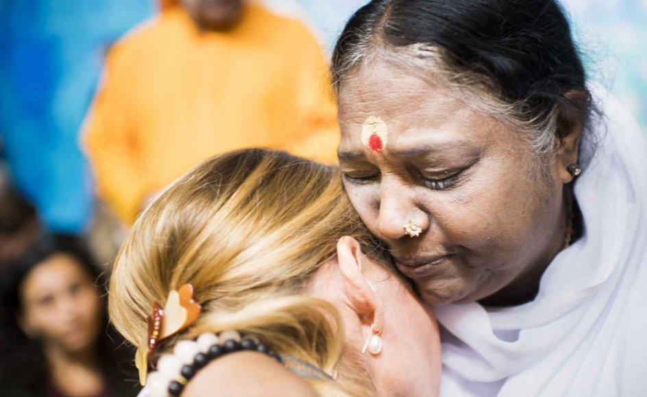 Godt 7000 danskere mødte op for at få et kram af den hinduistiske guru Amma, som med sit budskab om godhed i denne uge for første gang besøgte Danmark, her i kærlig omfavnelse med avisens journalist Else Marie Nygaard.