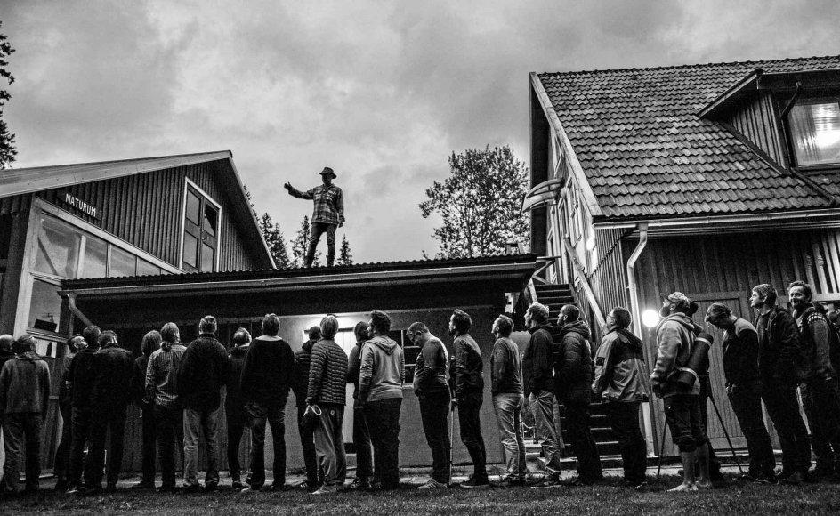 """40 mænd fra 22 forskellige lande er til """"European Men's Gathering"""" i Småland for at finde frem til, hvad det vil sige at være mand – for dem. Her er de på vej ind i fællessalen i en lang række med de ældste forrest og yngste bagerst. Over dem på et tag fortæller australske Arne Rubinstein, hvorfor det er vigtigt igen at ære de ældste. –"""