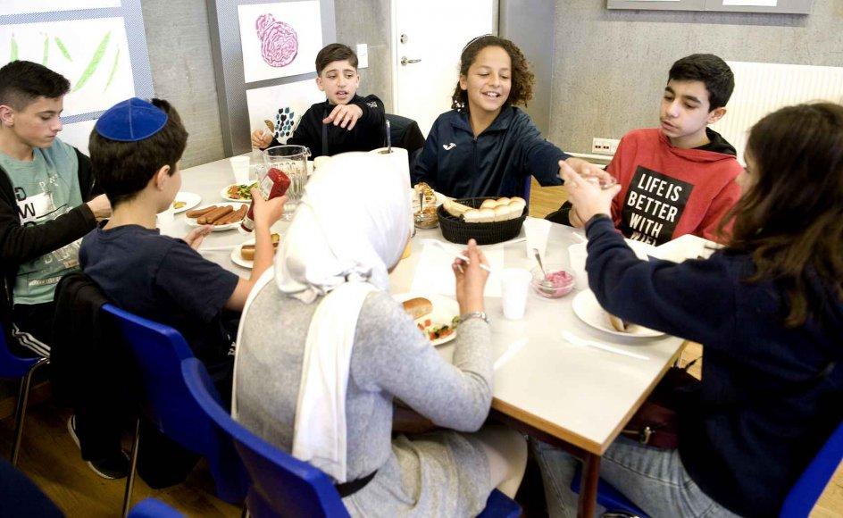 Yousef Ali Shaban og David Shlomi (øverst tv.) nød deres sojapølse-hotdog med de andre elever fra Al-Hikma- og Carolineskolen i fredags, da de som en del af et brobyggerprojekt mødtes for at få en bedre forståelse for hinanden. –