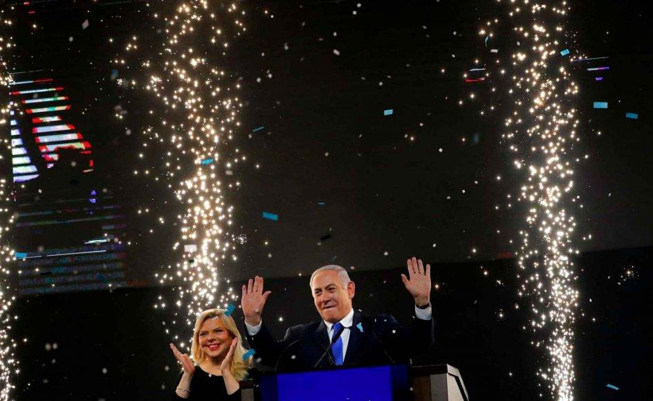 """""""Det er en kæmpesejr, en kæmpe sejr,"""" erklærede Netanyahu ud på de små nattetimer til sine jublende partifæller, mens hans hustru Sara forelsket kyssede ham under en regn af konfetti, og lyskastere tegnede dem en sejrsglorie."""