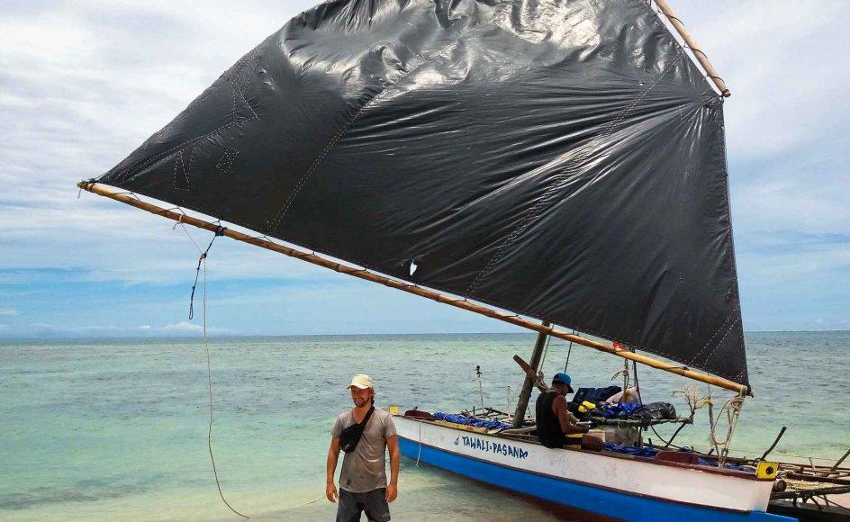 """Her står Thor Jensen foran den traditionelle fiskerkano, der var fartøjet, der bragte de fire rundt om verdens næststørste ø, Ny Guinea. Båden hedder """"Tawali Pasana"""", hvilket betyder """"revets skønhed"""" eller """"revets blomst"""" på det lokale sprog bwana bwana. – Privatfoto."""