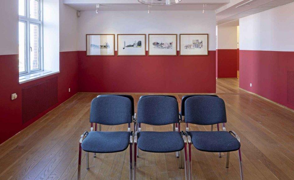 """3I udstillingens første rum findes det, der kan defineres som """"det offentlige rums"""" æstetik, som vi kender den fra venterum: Rummets møblement består af stolerækker placeret under informationshøjtalere, og væggene har en stringent rød stribe, som man kender fra hospitalets vægge, en banegård, en folkeskolegang, lægens venteværelse eller måske Borgerservice."""