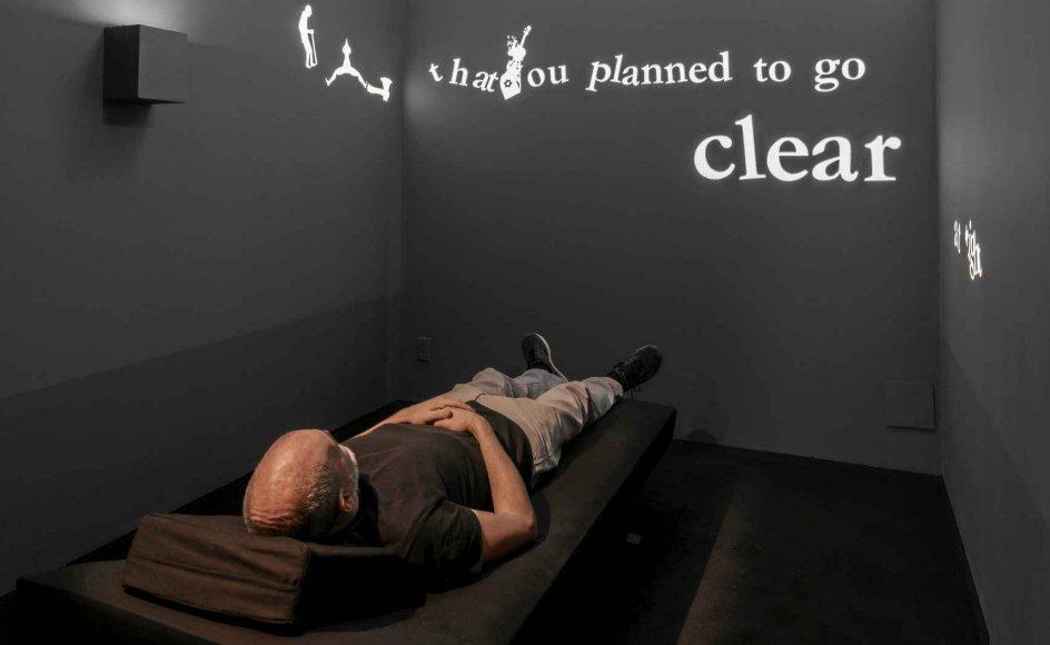 """Den israelske filminstruktør Ari Folman har til udstillingen indrettet et mørklagt """"Depression Room"""", hvor publikum lægger sig på en briks og lytter til Cohens nummer """"Famous Blue Raincoat"""" om paranoiaen, der breder sig, når man lever i et trekantsforhold. I løbet af denne session samler sangens hvide bogstaver og små piktogramagtige figurer sig og dækker successivt beskueren, der projiceres på en skærm i loftet. – Foto: Guy L'Heureux."""