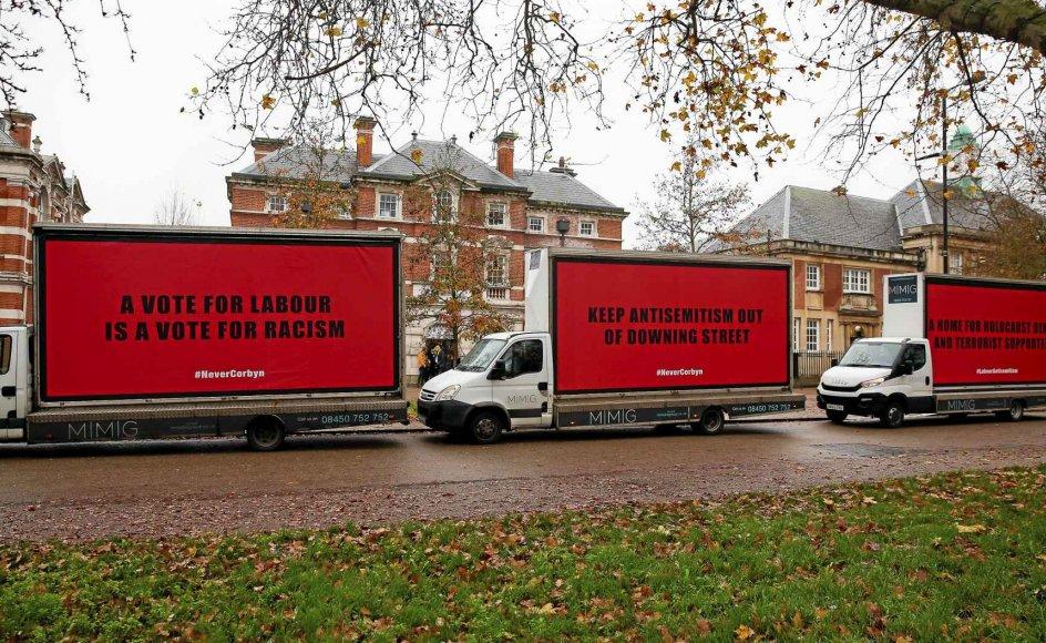 """Mens Labour i går lancerede sit valgprogram imod racisme og for religionsfrihed i London, havde kritikere, der anklager arbejderpartiet for antisemitisme, kørt store plakater i stilling udenfor for blandt andet at advare imod, at """"en stemme på Labour er en stemme for racisme"""". – Foto: xxxd/Riitzau Scanpix."""