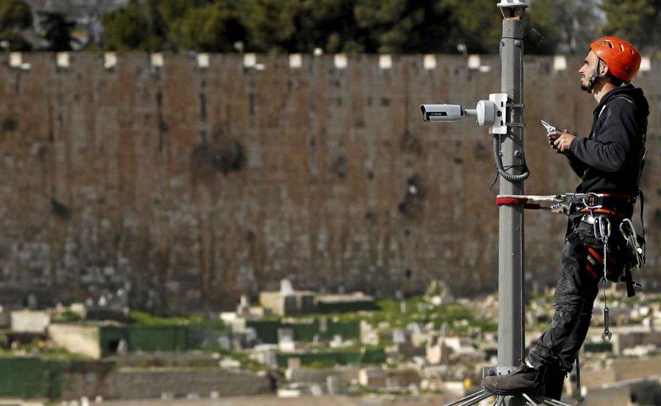 En israelsk tekniker ses her installere et overvågningskamera på en gade i det palæstinensiske kvarter Ras al-Amud med Klippemoskéen i baggrunden. – Foto: Ahmad Gharabli/AFP/Ritzau Scanpix.