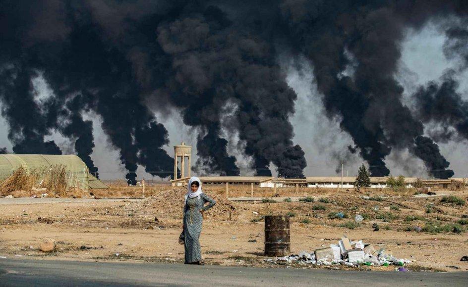 En kvinde står ved vejen udenfor den syriske by Tal Tamr nær den tyrkiske grænse.