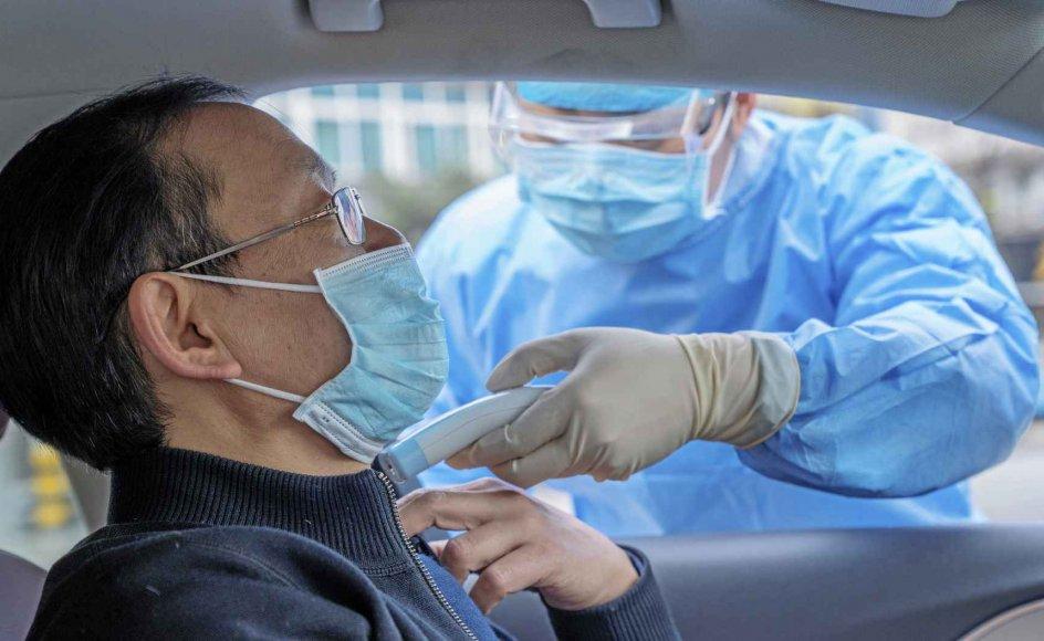 I Enshi tjekkes en bilists temperatur af en frivillig i beskyttelsesdragt i håb om at bremse corona-virusset. – Foto Xie Chuanhui/Costfoto/Sipa USA/Ritzau Scanpix.