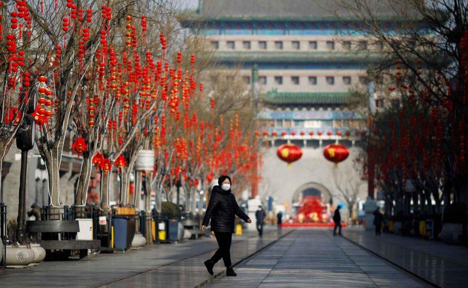 En kvinde går med ansigtsmaske ned ad gågaden Qianmen i Beijing. Gaden summer normalt af liv, men siden coronaepidemiens udbrud har den oftere ligget øde.