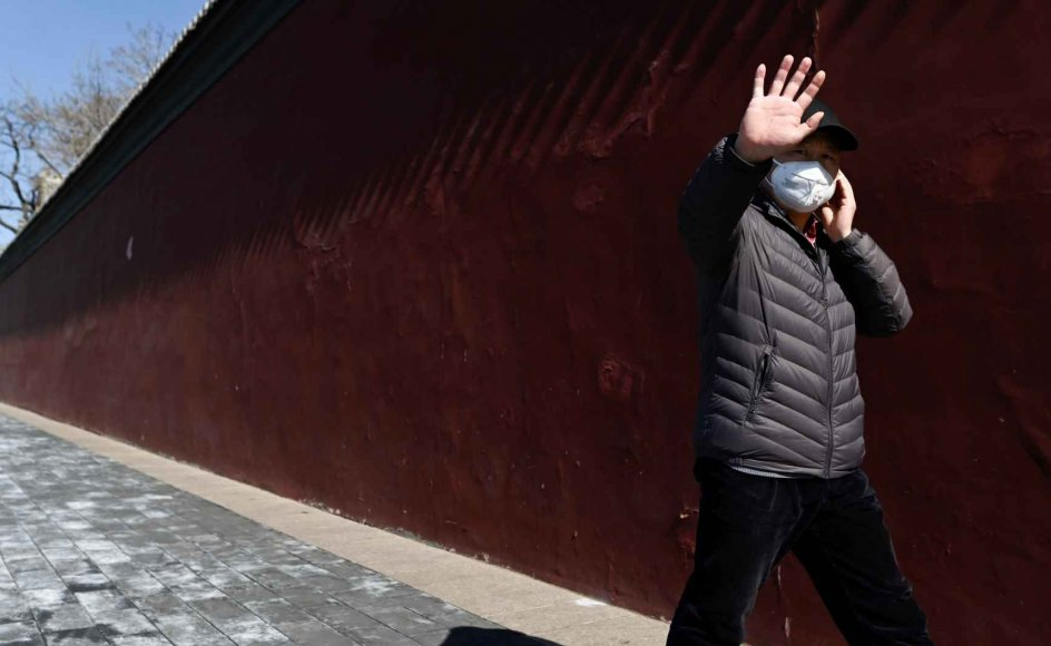 En mand vinker i Beijing. Verdenssundhedsorganisationen (WHO) opfordrer til, at man udskifter håndtrykket med andre måder at hilse på hinanden på. Flere steder i verden dukker nye alternative måder at hilse på hinanden på op. (Arkivfoto)
