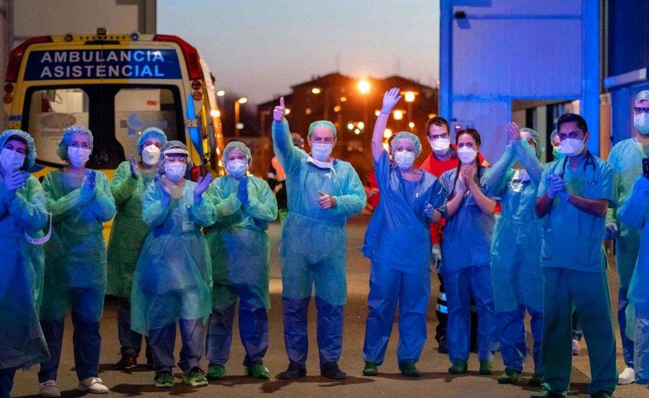 Spanien er med næsten 50.000 coronasmittede nu det fjerdehårdest ramte land i verden efter Kina, Italien og USA – og ligger sammen med Italien i front, hvad angår dødstal. Her er det sundhedspersonale på centralsygehuset i nordspanske Burgos, der vinker til folk, som trods udgangsforbuddet er mødt frem for i fælleskab at hylde og klappe ad de hårdt arbejdende læger og sygeplejersker på hospitalet. – Foto: Cesar Manso/AFP/Ritzau Scanpix.