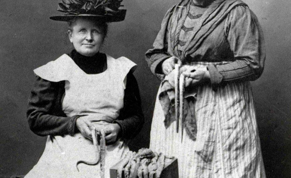 På torvedage i Randers solgte Hansigne Schmidt og Caroline Larsen ål, som blev fanget af lokale fiskere i de indre farvande. Torvekonerne er her fotograferet med ål i fotografens atelier i begyndelsen 1900-tallet. – Foto: Randers Stadsarkiv.