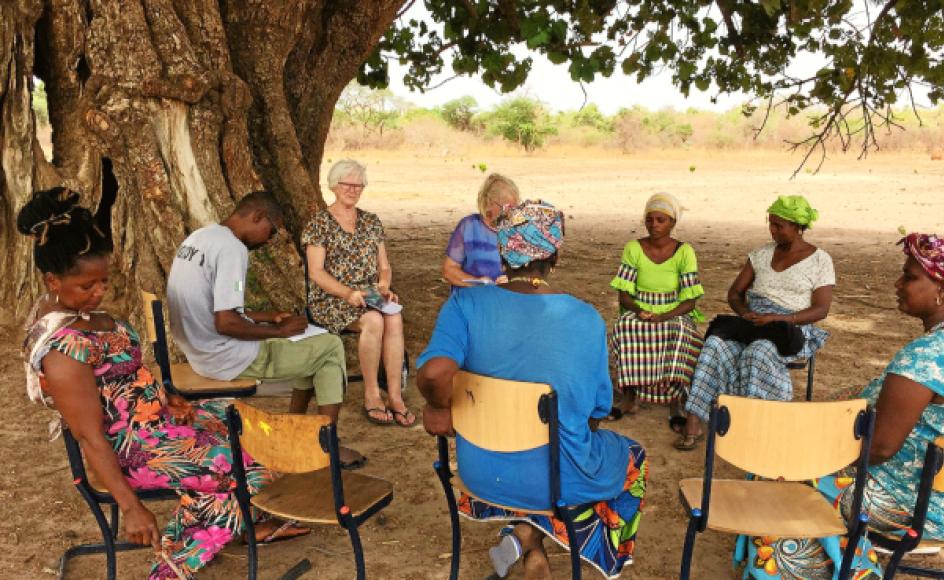 """Thea Lauridsen og Ruth Noer holder, med hjælp fra en tolk, møde med en kvindegruppe i en landsby i Gambia. De to danskere ved godt, at det frivillige arbejde kan synes som en dråbe i havet, men vi """"kan være med til at ændre og udvikle noget, der hjælper nogle afrikanske landsbybeboere ud af fattigdom, dårlig hygiejne og analfabetisme, og som blandt andet kan gøre, at unge bliver i deres hjemland – i stedet for at tage over Middelhavet, hvor vi efterhånden ved, hvor det ender,"""" fortæller de."""